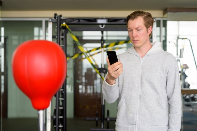 Young man using phone and ready for boxing at the gym