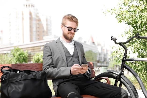 公園で自転車とベンチに座って電話を使用して若い男