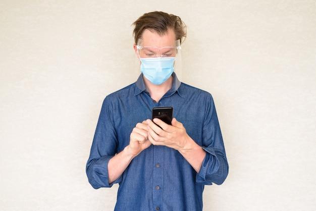 Молодой человек с помощью телефона с маской и щитком на бетонной стене
