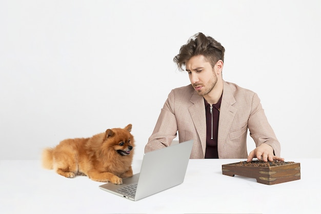 Young man using russian abacus while spitz dog sitting near the notebook