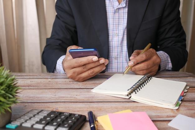 Молодой человек с помощью смартфона и записи в блокноте в то время как расположен