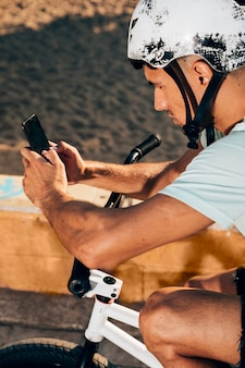 Young man using smart phone on his bike