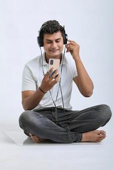 スマートフォンとヘッドフォンアクセサリーを使用して若い男。