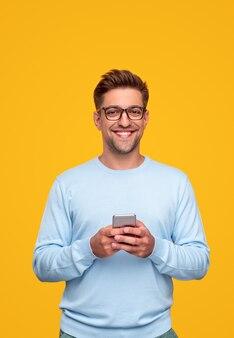 Молодой человек с помощью смартфона и улыбается