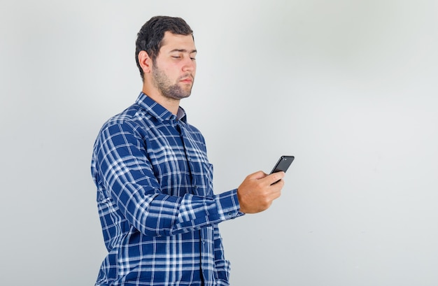 Young man using smartphone in checked shirt and looking careful.