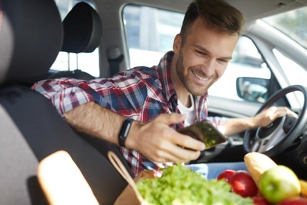 車の中でスマートフォンを使用して若い男