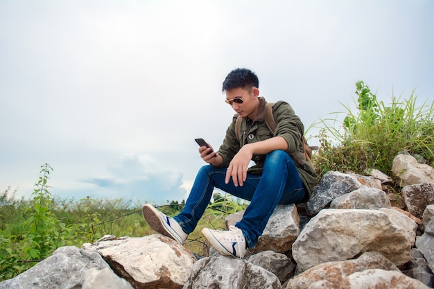 Young man using smartphone. man holding mobile smartphone using app texting sms message.