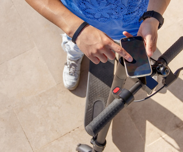 Young man using smartphone to unlock a shared electric scooter close up