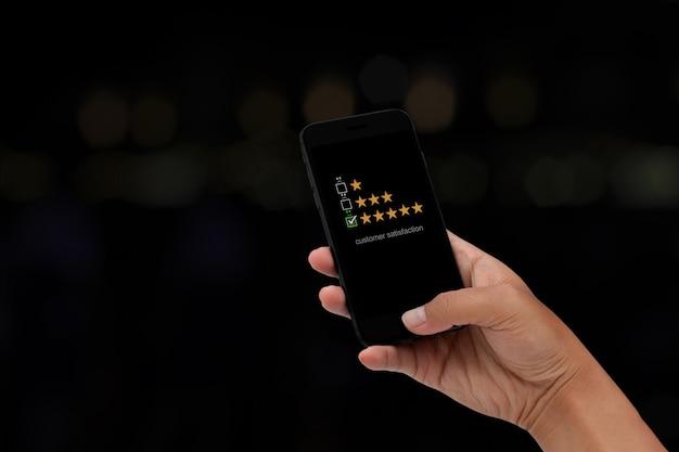 디지털 터치 스크린의 웃는 얼굴 아이콘에 가상 화면이 있는 스마트폰을 사용하는 청년. 고객 서비스 평가 개념입니다.