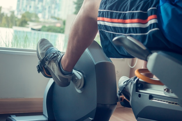 Young man using a spinning bike in an indoor fitness center