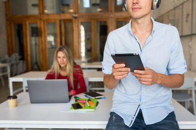 若い男がタブレットを使用して、ヘッドフォンで音楽を聴く