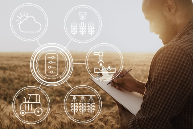 Young man using tablet in wheat field close up, agricultural concept