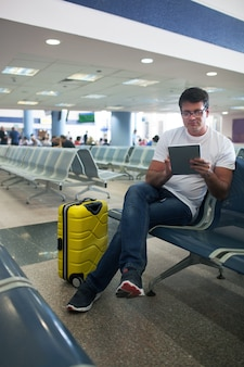 Young man using touch pad in the airport lounge