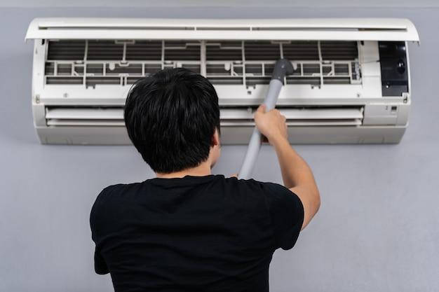 Молодой человек с помощью пылесоса для очистки кондиционера дома