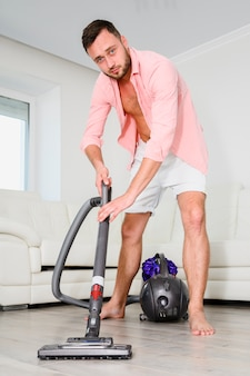 Young man using the vacuum cleaner