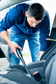 자동차 내부 청소를 위해 진공을 사용하는 젊은 남자