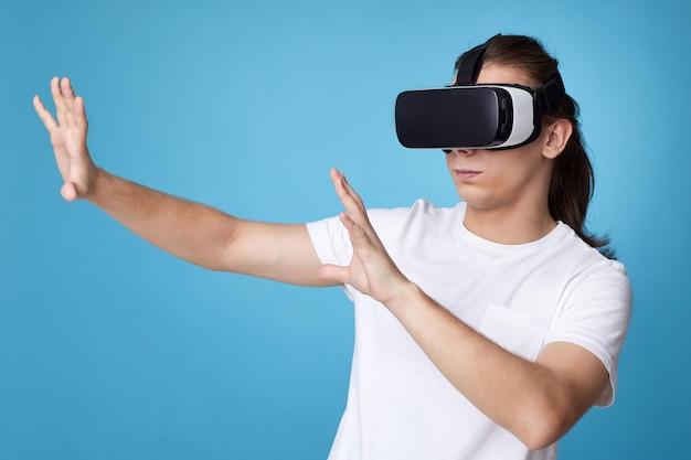 Молодой человек с помощью гарнитуры виртуальной реальности. гаджеты