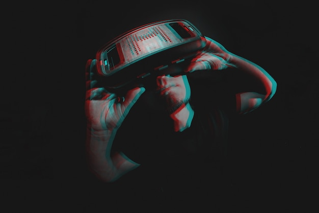 Young man using virtual reality headset vr. education online, studying concept. black and white with 3d glitch virtual reality effect