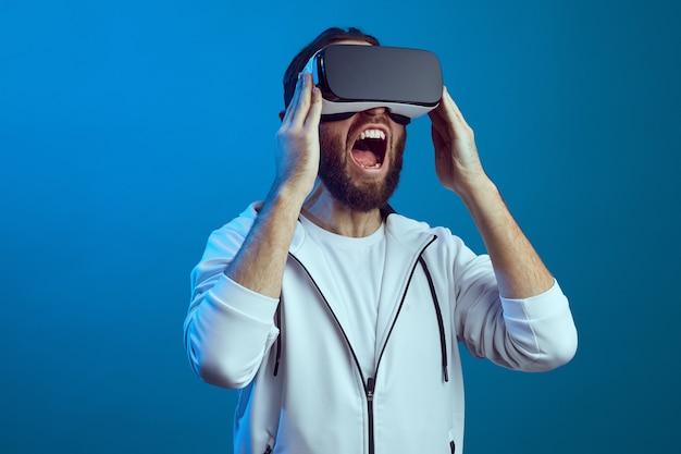 Молодой человек с помощью гарнитуры виртуальной реальности vr future gadgets technology