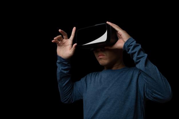 Молодой человек с помощью гарнитуры виртуальной реальности. vr, будущее, онлайн-концепция технологий. темный фон.