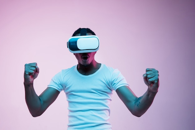 Young man using vr glasses in neon light