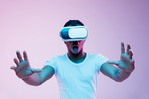 Young man using vr-glasses with neon lights