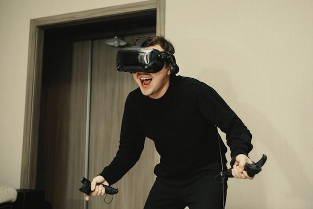 コンピューターを再生するためにvrゴーグルを使用している若い男。若い男セレクティブフォーカス。