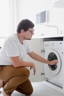 Молодой человек, использующий стиральную машину в день стирки дома