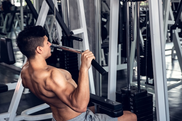 Young man using weight lifting equipment to build a massive chest and arm at indoor sport gym.