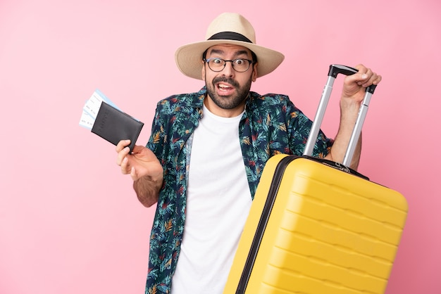 Young man in vacation with suitcase and passport and surprised