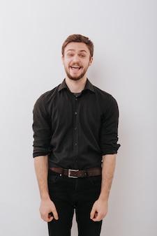 若い男は非常に満足して、黒いシャツで口を開けて、カメラ、孤立したスペースグレー、コピースペースを見てください。