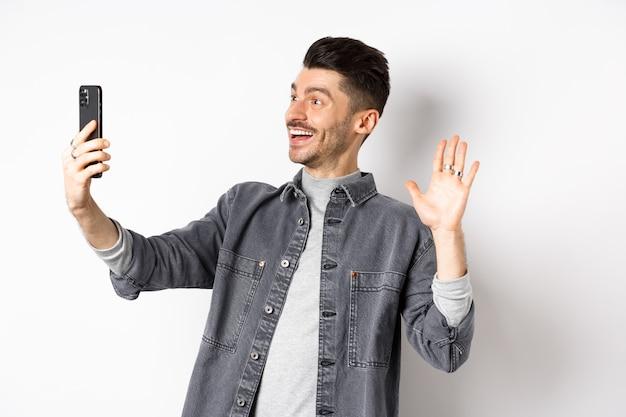 젊은 남자 비디오 휴대 전화 채팅, 스마트 폰 카메라에 손을 포기, 온라인 친구 인사, 흰색 바탕에 서 서.