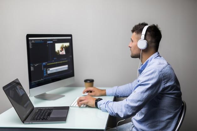 若い男のビデオグラファーは彼のオフィスで彼のパソコンで映像と音を編集してカットします