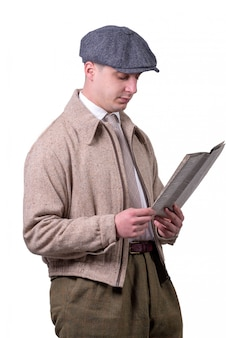 Young man in vintage clothes with hat, reading newspaper