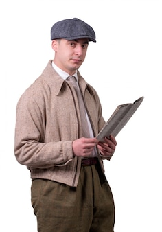 Young man in vintage clothes with hat, reading a newspaper