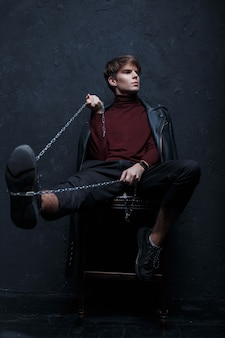 Young man in a vintage jacket in a stylish burgundy golf in black pants and stylish sneakers posing sitting on a chair and holding a silver chain in his hands in the studio near the wall.nice  guy