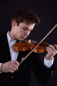 若い男のバイオリニストがクラシック音楽を演奏