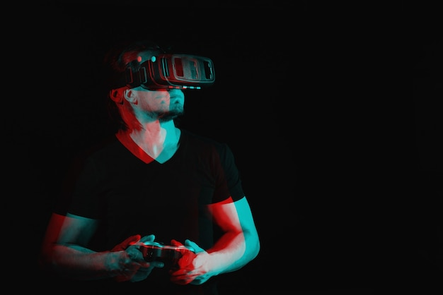 A young man in virtual reality glasses is playing video games. with space for text. black and white with 3d glitch virtual reality effect