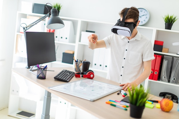 A young man in virtual reality glasses stands near the table and pulls his arm up. a young man thumbs a virtual page.