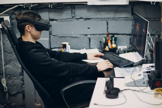 Young man in virtual reality goggles, vr glasses headset sitting at computer