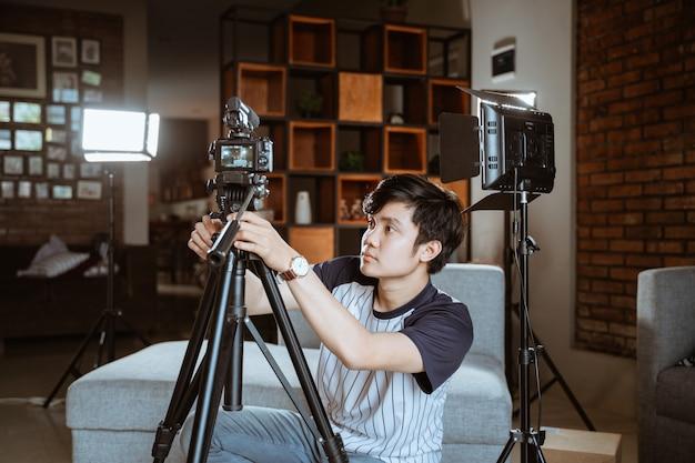 Молодой человек влоггер готовит камеру для создания своего влог