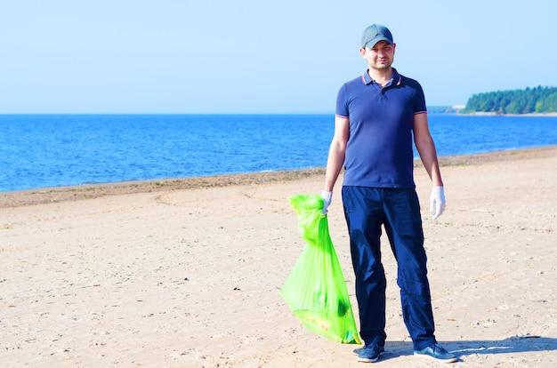 Молодой человек-волонтер убирает мусор на пляже и в воде в зеленой экологической сумке.