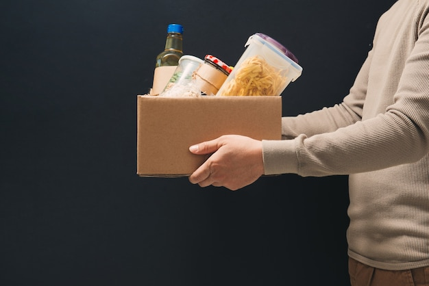 A young man volunteer is holding a donation box with foodstuffs.
