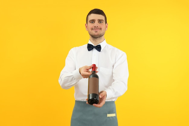 Young man waiter holds bottle of wine on yellow background.