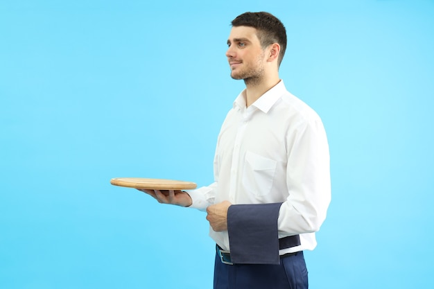 Young man waiter holds tray and towel on blue background.