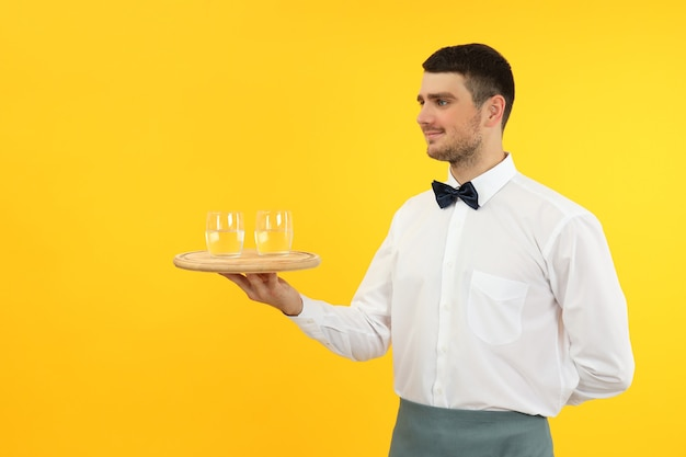 Young man waiter holds tray with glasses of water on yellow background.