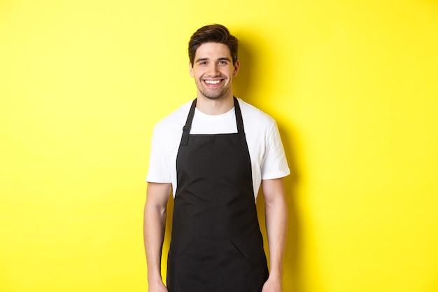 Официант молодой человек в черном фартуке улыбается, работая в магазине или кафе, стоя на желтой спине ...