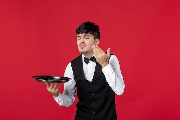 Young man waiter in a uniform tying butterfly on neck holding tray smelling on isolated red background