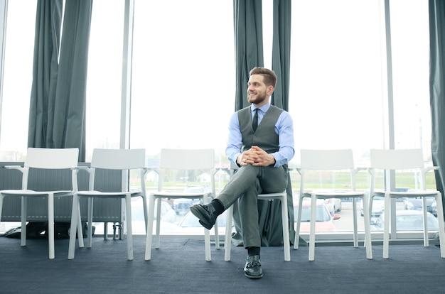 실내에서 면접을 기다리는 젊은 남자.