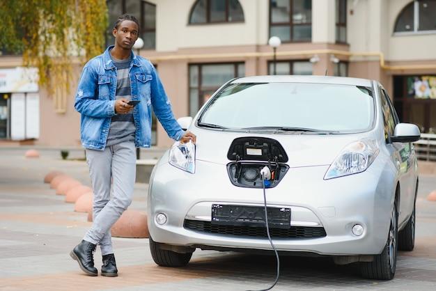 Молодой человек ждет зарядки своего электромобиля